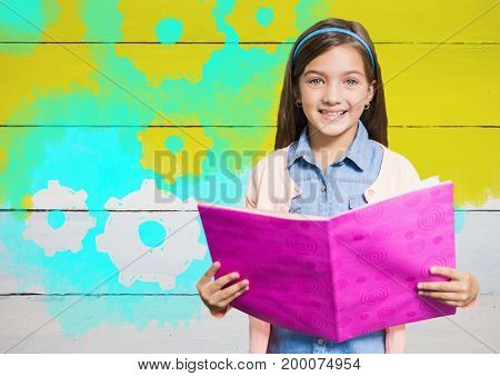Digital composite of Girl holding book in front of yellow painted wall with cog gear settings