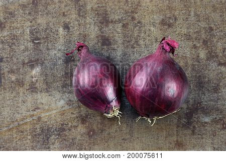 two red onions on a grungy metal background