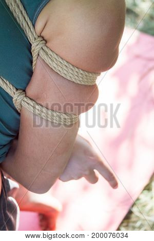 Shibari in nature in summer. A tied up young Indian-type girl with a blindfold hung on a tree. Bridge of trust Shibari Dragonfly. Selective focus.