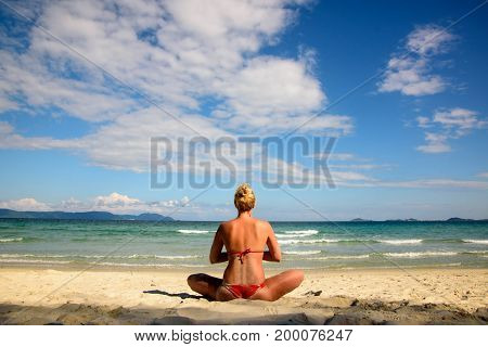 Woman meditating on beach in lotus position. View from the back