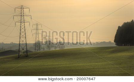 Electricity Cable Communication Towers On Sunrise Landscape