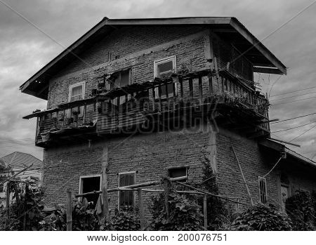 Black and white dramatic photo of house made of red bricks.