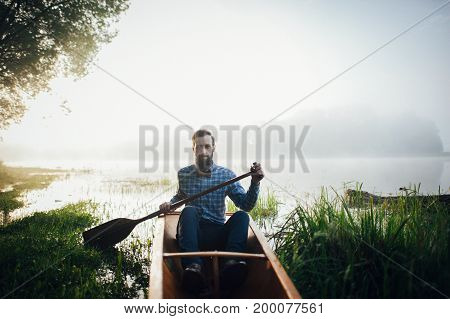 handsome man lying with paddle in canoe on green grass