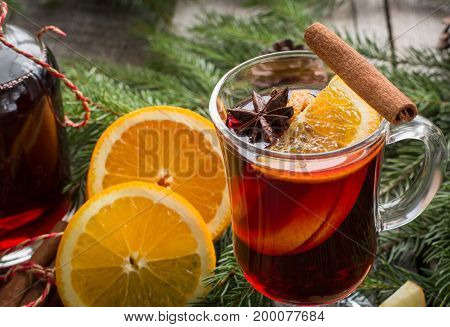 Christmas tradition drink. Hot Mulled wine with cinnamon and christmas tree on black slate dish. Close up, copy space.