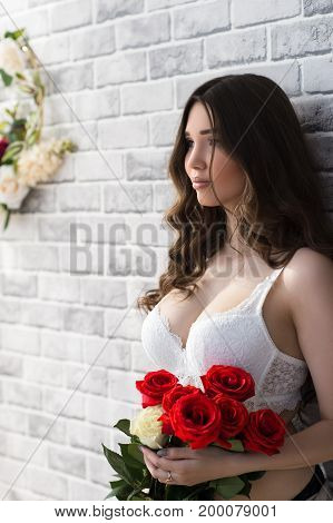 charming attractive woman with bouquet roses with white bra
