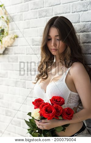 sensual attractive woman with bouquet roses closeup
