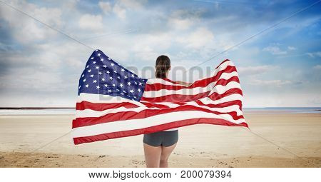 Digital composite of Woman holding a USA flag in the beach