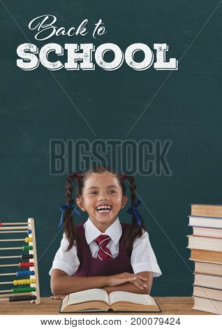 Digital composite of Happy student girl at table against green blackboard with back to school text
