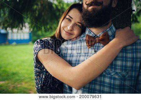 wife affectionately hugging husband while standing in garden