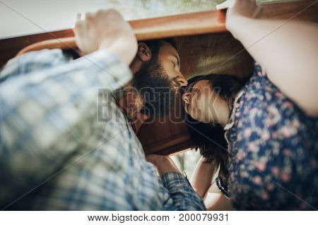 romantic couple in love kissing while holding canoe above heads