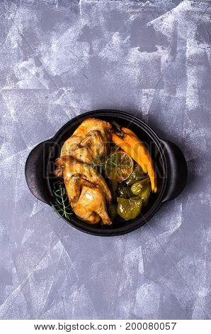 Halved baked chicken with vegetables and spices. Selective focus.