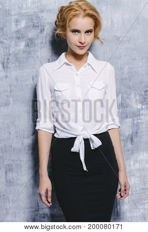 Beautiful young business woman smiling at camera. Fashion, business style.