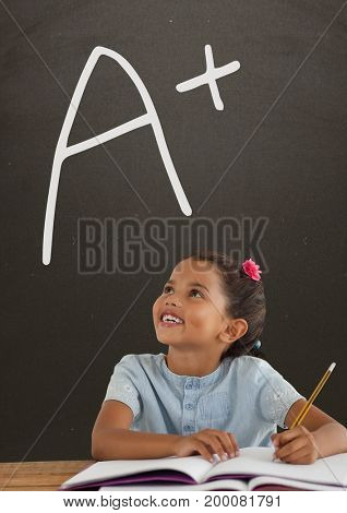 Digital composite of Happy student girl at table looking up against grey blackboard with A+ text