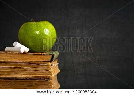 Chalk And Green Apple On Old Textbook