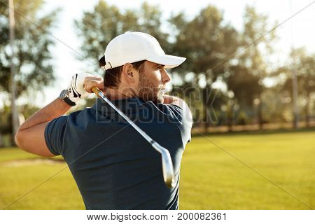 Close up of a young concentrated man shooting golf ball while playing at the green course