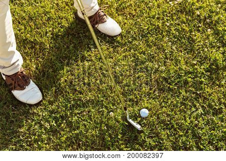 Close-up of male golfer teeing off while standing on golf course