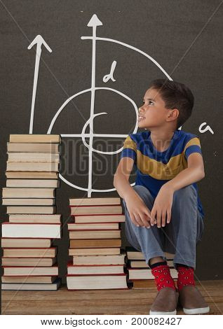Digital composite of Student boy on a table looking up against grey blackboard with school and education graphic