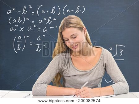 Digital composite of Student girl at table writing against blue blackboard with education and school graphics