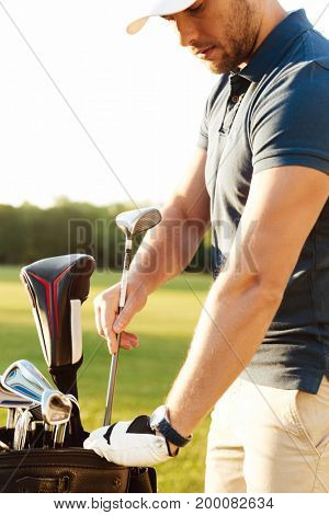Young focused man golfer taking out the golf club from a bag while standing on a field