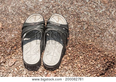 Black slippers on the sand beach with relaxing waves