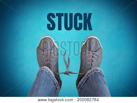 Digital composite of Stuck text and  and grey shoes on feet with blue background