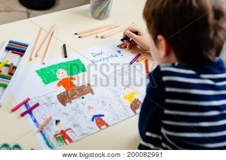 Little Child Draws A Pastel Drawing Of His Teacher In School Class.