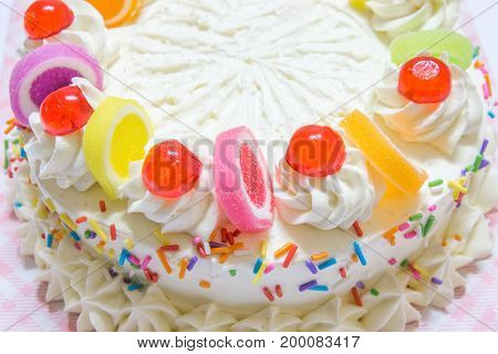 Closeup Of White Birthday Cake With Colorful Jelly And Cream On White Background. Select Focus