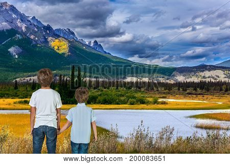 Magnificent landscape in the Rocky Mountains. Two lovely boys admire the beauty of mountains and lakes. The concept of ecological and active tourism