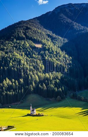Sunny day in Dolomites, Tirol.  The symbol of the valley Val di Funes - church of Santa Maddalena. Forested mountains surrounded by green Alpine meadows
