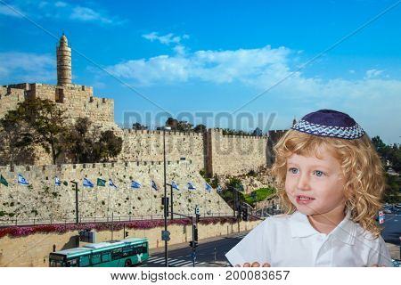 The Jewish holiday of Sukkot. Cute little boy with long blond curls and blue eyes in a knitted skullcap. He stands against the backdrop of the castle walls of Jerusalem