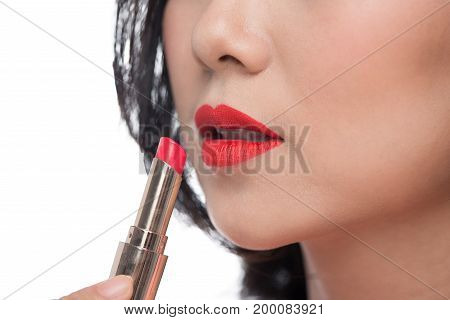 Pretty asian young woman applying red matt lipstick on her lips