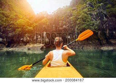 Purposeful цoman paddling the kayak in the calm bay Halong among picturesque karst mountains at sunset.Vietnam. Mountains and sea landscape travel to Asia happiness emotion summer holiday concept.