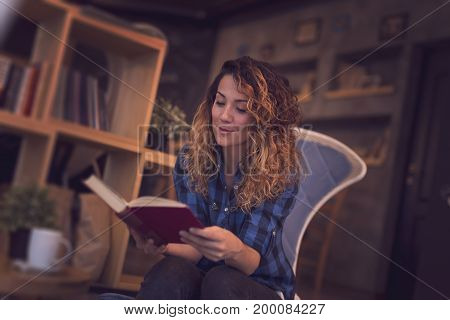Beautiful young woman sitting in a coffee shop enjoying her morning coffee and reading a book