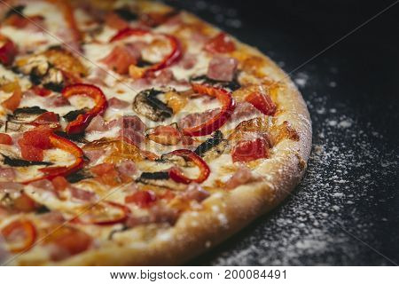 Delicious Pizza Fresh Hot Closeup On Black Table With Scattered Flour