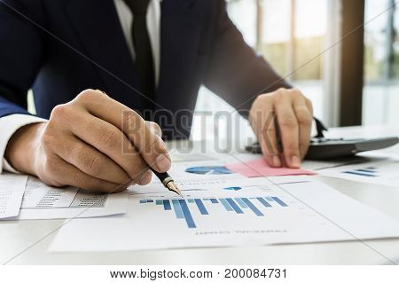 Close up Business man using calculator and laptop computer for calculating with finance paper tax accounting Finance concept.