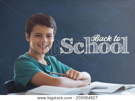 Digital composite of Student boy at table against blue blackboard with back to school text