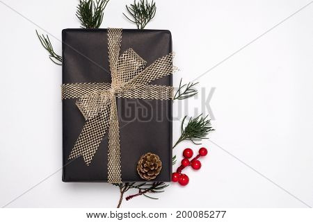 Christmas present gift boxes with decoration of fir leaves holly berry and pine cone on white background. Creative Flat layout and top view design.