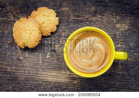 Cup of coffee with cookies on rustic wooden table with place for text. Yellow coffee mug. Bright autumn still life against autumn depression. Coffee break concept. Top view. Copy space.