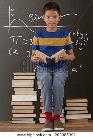 Digital composite of Happy student boy on a table reading against grey blackboard with education and school graphics