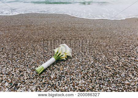 A Bouquet Of White Callas Lies On The Seashore