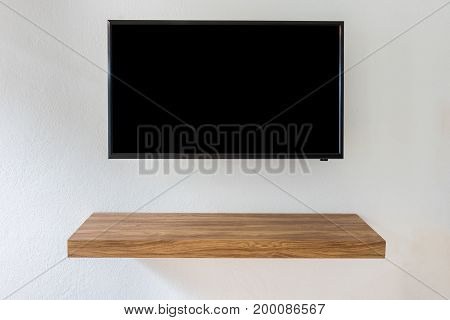 Black LED tv television screen on white wall background with modern wooden table in room.