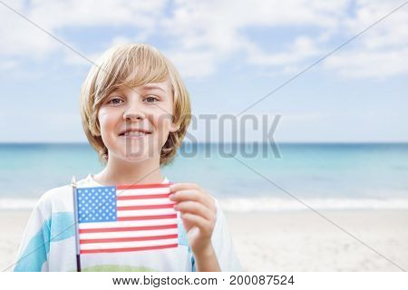 Digital composite of Happy boy holding a USA flag in the beach