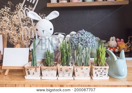 Cute prop on wooden table in room with bunny stuffed toys and cactus tree in pot. vintage style. copy space background