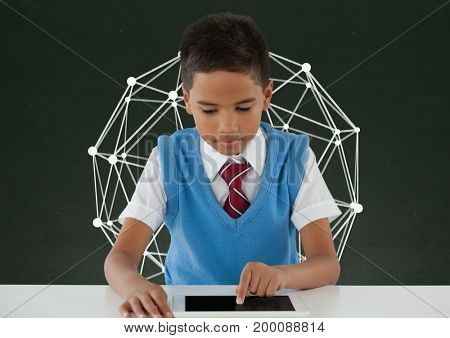 Digital composite of Student boy at table using a tablet against green blackboard with education graphic