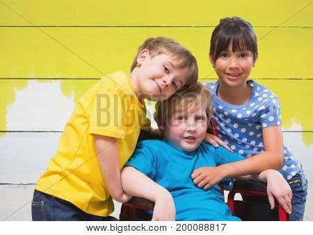 Digital composite of Disabled boy in wheelchair with friends with bright painted yellow wood background
