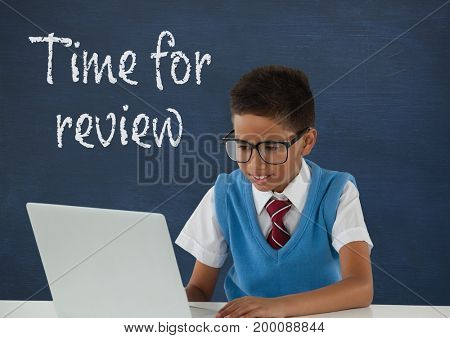 Digital composite of Student boy at table using a computer against blue blackboard with time for review text