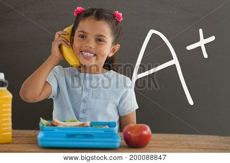 Digital composite of Happy student girl at table holding a banana against grey blackboard with A+ text