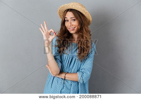 Image of happy young pretty woman standing over grey wall wearing hat showing okay gesture. Looking camera.