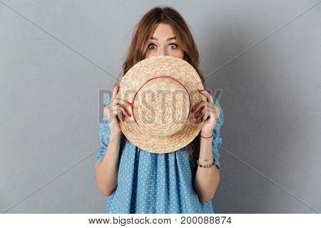 Image of young pretty woman standing over grey wall covering face with hat. Looking camera.