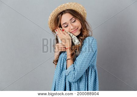 Image of young cheerful woman standing over grey wall wearing hat holding money. Eyes closed.
